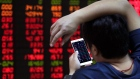 A man checks stock index through his smartphone at a brokerage house in Beijing Sept. 18, 2017