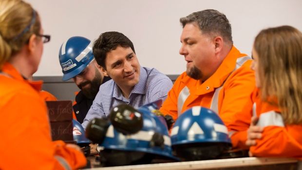 Prime Minister Justin Trudeau speaks with workers during a visit to Stelco Hamilton