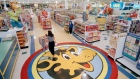 In this July 30, 1996, file photo, a woman pushes a shopping cart over a graphic of Toys R Us masc