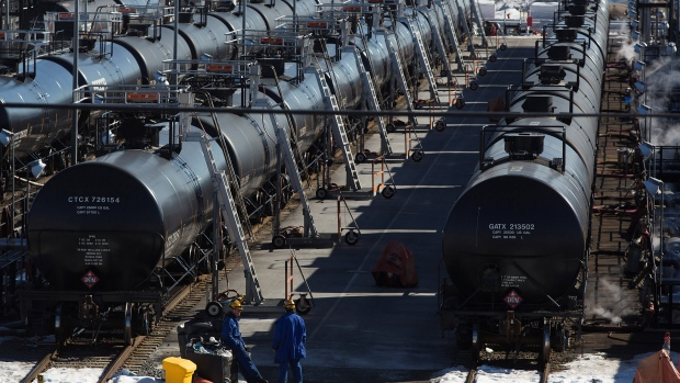 Irving Oil workers inspect rail cars carrying crude oil at the Irving Oil rail yard terminal