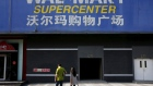 FILE PHOTO: Pedestrians walk past a signboard of Wal-Mart at its branch store in Beijing