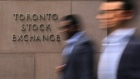 Businessmen pass the Toronto Stock Exchange sign in Toronto