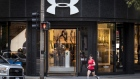 A woman runs past an Under Armour Inc. store in downtown Chicago, Illinois, U.S., on Monday, Oct. 16, 2017. Under Armour must improve and expand its footwear business to counter constant challenges to its apparel market share from new entrants, most recently Amazon.com.