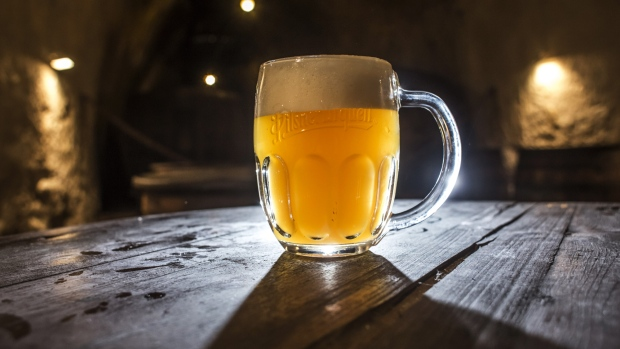 A glass of beer sits on a table near wooden vats at the Pilsner Urquell brewery, operated by SABMiller Plc, in Plzen, Czech Republic, on Monday, Dec. 7, 2015. Carrying the Czech Beer label requires the use of specific types of Czech-grown barley and hops that give the domestic brew its characteristic bitterness, aroma and drinkability, said Vladimir Balach, the head of the Czech Beer and Malt Association in a 2014 interview.