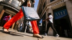 A shopper caries a Zara clothing retailer bag as shes passes a Gap Inc. retail store, left, and a Coach retail store in Regent Street in London, U.K., on Tuesday, April 17, 2018.