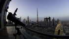 A telescope sits on the outdoor deck of a skyscraper overlooking the city skyline towards the Burj Khalifa tower, center, and the Address Sky View, center right, under construction by developers Emaar Properties PJSC, in Dubai, United Arab Emirates, on Wednesday, April 11, 2018. Transformed into a flamboyant city state from an impoverished Gulf port in less than 50 years, Dubai defied geology to build skyscrapers and elaborately shaped islands in the sea.
