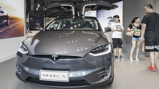 Customers look at a Tesla Motors Inc. Model X electric vehicle on display at the company's showroom in Shanghai.
