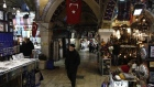 A pedestrian walks past retail stores in the Grand Bazaar in Istanbul. Photographer: Kostas Tsironis/Bloomberg