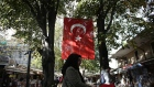 A Turkish national flag hangs between trees in a street lined with shops in Istanbul, Turkey, on Tuesday, Nov. 21, 2017. Investors looking at Turkey are nearly unanimous in their view of the central bank's latest moves to try and prop up the lira: Not enough.