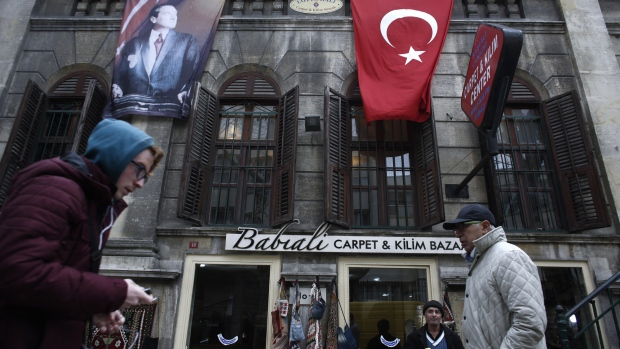 Pedestrians pass a carpet store decorated with a Turkish national flag and image of Kemal Ataturk, founder of modern Turkey, in Istanbul, Turkey, on Tuesday, Jan. 3, 2017. Turkey's lira weakened the most among major world currencies on Tuesday, falling as much as 1.7 percent to a new record, as the killer of 39 people at an Istanbul nightclub remained at large and inflation accelerated more than estimates in December.