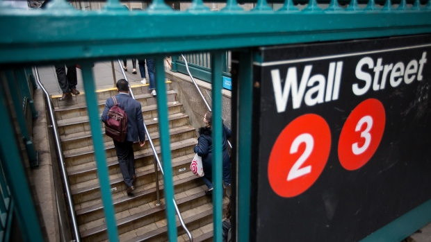 Commuters exit the Wall Street subway station near the New York Stock Exchange (NYSE) in New York, U.S., on Monday, May 14, 2018. U.S. stocks edged higher as trade tensions between the world's two biggest economies showed signs of abating.