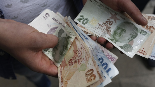 A customer counts Turkish lira banknotes after visiting a currency exchange in Istanbul Turkey on Friday