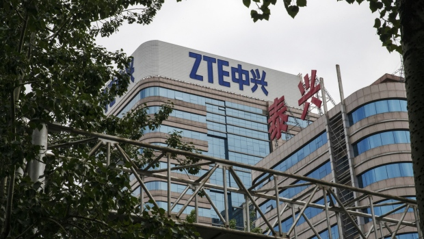 "Signage is displayed atop a ZTE Corp. building in Beijing, China, on Thursday, May 24, 2018. President Donald Trump said the U.S. would allow Chinese telecommunications-equipment maker ZTE Corp. to remain in business after paying a $1.3 billion fine, changing its management and board and providing ""high-level security guarantees."" Photographer: Gilles Sabrie/Bloomberg"
