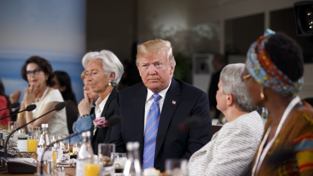 U.S. President Donald Trump, center, sits after arriving late for the Group of Seven (G7) Gender Equality Advisory Council Breakfast at the G7 Leaders Summit in La Malbaie, Quebec, Canada, on Saturday, June 9, 2018. Trump proposed the complete elimination of all barriers to international trade at a Group of Seven summit, a move that turns the tables on allies who accuse the U.S. of wielding protectionist policies. Photographer: Cole Burston/Bloomberg