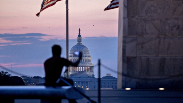 The U.S. Capitol building stands past a visitor taking a photograph at the Washington Monument before sunrise in Washington, D.C., U.S., on Tuesday, July 11, 2017. As Congress returned from its mid-summer break yesterday for a crucial three-week stretch, several obstacles await lawmakers, including an ongoing health-care fight, divisions among Republicans on the basic parameters of a tax bill, and a maelstrom of upcoming deadlines to keep the government running and avert a catastrophic default on U.S. debt.