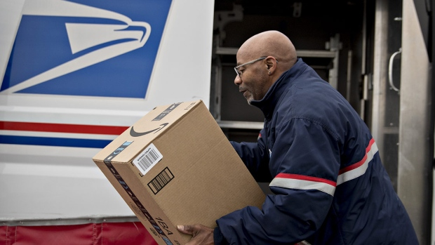 A letter carrier lifts an Amazon.com Inc. package from a bin while preparing a vehicle for deliveries at the United States Postal Service (USPS) Joseph Curseen Jr. and Thomas Morris Jr. processing and distribution center in Washington, D.C., U.S., on Tuesday, Dec. 12, 2017. The USPS said it expects to deliver over 15 billion total pieces of mail this holiday season with expanded Sunday delivery operations in certain areas, delivering over six million packages each Sunday in December.