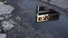 Exxon Mobil Corp. signage is reflected in a puddle at a gas station in Nashport, Ohio, U.S., on Friday, Jan. 26, 2018.