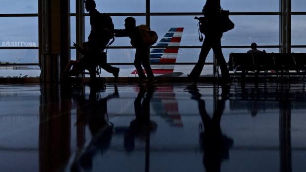 Travelers walk past an American Airlines Group Inc. aircraft at Ronald Reagan National Airport (DCA) in Washington, D.C., U.S., on Wednesday, Nov. 22, 2017. The trade association Airlines for America has projected that 28.5 million passengers will travel on U.S. airlines during the 12-day Thanksgiving air-travel period, up 3 percent from 2016.