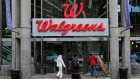 In this June 4, 2014, file photo, people walk in to a Walgreens retail store in Boston.
