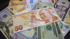 Turkish lira and dollar banknotes sit in this arranged photo at a currency exchange bureau in Istanb