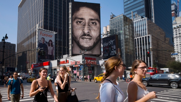 People walk by a Nike advertisement featuring Colin Kaepernick on display in New York, Sept. 5, 2018