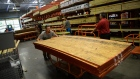A customer pushes a cart with plywood at Home Depot ahead of Hurricane Florence in North Carolina