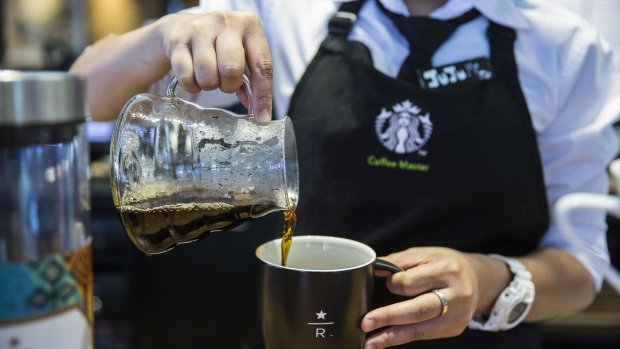 An employee pours coffee from a glass jug into a mug at a Starbucks Corp. coffee shop
