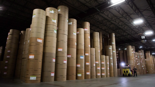 Rolls of paper tower above workers at Catalyst Paper's distribution centre in Surrey, B.C.