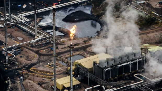 Flames shoot from a flare at the Suncor Energy Inc. Millennium upgrader plant in this aerial photograph taken above the Athabasca oil sands near Fort McMurray, Alberta, Canada, on Monday, Sept. 10, 2018. While the upfront spending on a mine tends to be costlier than developing more common oil-sands wells, their decades-long lifespans can make them lucrative in the future for companies willing to wait.
