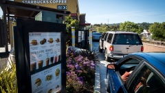 Customers wait in line to make a purchase at the drive-thru of a Starbucks Corp. coffee shop in Pinole, California.