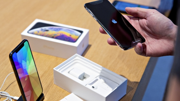 A customer view an Apple Inc. iPhone XS during a sales launch at a store in Chicago, Illinois, U.S., on Friday, Sept. 21, 2018. The iPhone XS is up to $200 more expensive than last years already pricey iPhone X and represents one of the smallest advances in the product lines history. But that means little to the Apple Inc. faithful or those seeking to upgrade their older iPhone.