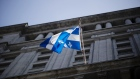 A Quebec flag flies outside the Sun Life building in Montreal, Quebec, Canada, on Monday, Aug. 20, 2018. Median single-family home prices in Montreal rose 5.7% to C$336,250 in July from a year ago, according to the Greater Montreal Real Estate Board (GMREB).