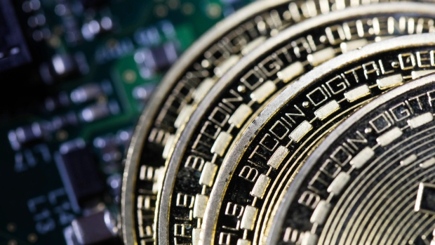 Three coins representing bitcoin cryptocurrency sit on a computer circuit board in this arranged photograph in london u k
