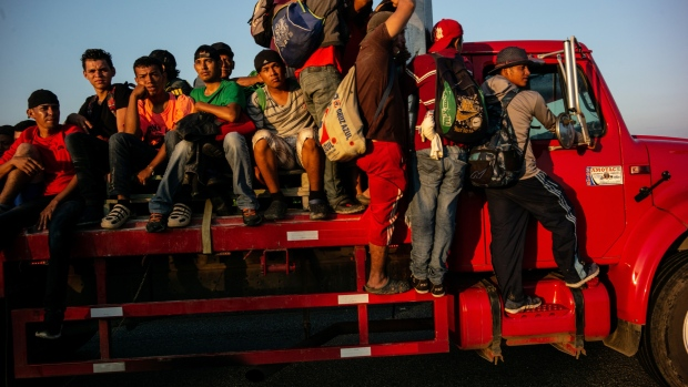 Central American refugees and asylum seekers ride on a cargo truck moving towards Mapastepec in Escuincla, Chiapas state, Mexico, on Wednesday, Oct. 24, 2018.