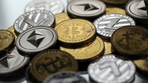 A collection of bitcoin litecoin and ethereum tokens sit in this arranged photograph in danbury u k on tuesday oct 17 2017