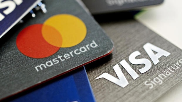 Visa Inc. and Mastercard Inc. credit cards are arranged for a photograph in Tiskilwa, Illinois, U.S., on Tuesday, Sept. 18, 2018. Visa and Mastercard agreed to pay as much as $6.2 billion to end a long-running price-fixing case brought by merchants over card fees, the largest-ever class action settlement of an antitrust case.