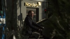 Cyclists wait in traffic near a Nordea Bank AB branch in Copenhagen, Denmark, on Tuesday, Nov. 12, 2013.