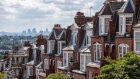 A terraced row of residential housing sit in the Muswell Hill district, in view of the Canary Wharf financial, business and shopping district of London, U.K., on Tuesday, July 31, 2018. U.K. house prices bucked their recent trend with a modest pick up in growth in July, according to Nationwide Building Society.