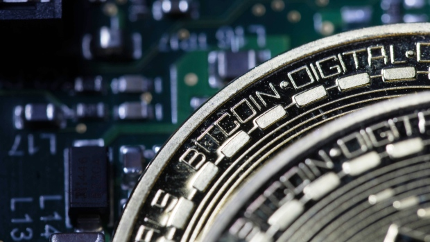 Two coins representing Bitcoin cryptocurrency sit on a computer circuit board in this arranged photograph in London, U.K.