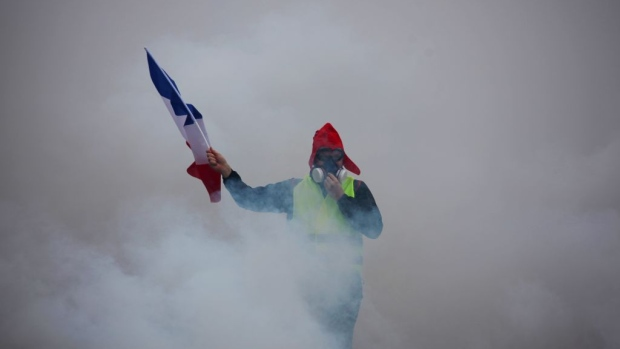 A demonstrator holds a French flag as he walks amid the tear gas during a protest of Yellow vests (Gilets jaunes) against rising oil prices and living costs, on December 1, 2018 in Paris.