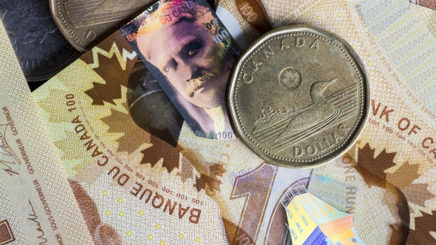 "Canadian one dollar coins, also known as Loonies, and Canadian one hundred dollar banknotes are arranged for a photograph in Toronto, Ontario, Canada, on Wednesday, July 25, 2018. One of Prime Minister Justin Trudeau's envoys said the government would respond ""proportionally"" if the U.S. imposes tariffs on vehicles and parts, though Canada hasn't begun preparing any formal retaliatory package, two people familiar with the matter said."