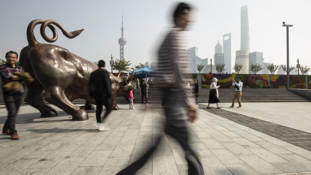 People take photographs with the Bund Bull statue in Shanghai, China, on Wednesday, Oct. 24, 2018.