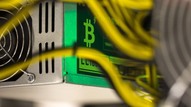 A bitcoin logo sits on a LL 1800W power unit supplying cryptocurrency mining machines at the SberBit mining \'hotel\' in Moscow, Russia, on Saturday, Dec. 9, 2017. Futures on the world's most popular cryptocurrency surged as much as 26 percent in their debut session on Cboe Global Markets Inc.\'s exchange, triggering two temporary trading halts designed to calm the market.