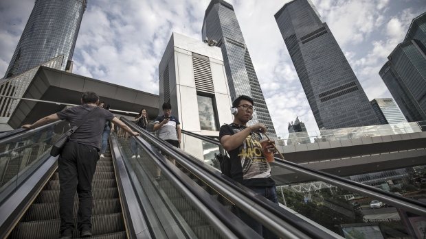 Pedestrians ride an escalator in the Lujiazui Financial District in Shanghai, China, on Monday, Sept. 4, 2017. The Chinese central bank's tight leash on liquidity is straining the bond market, with the benchmark sovereign yield climbing to near the highest level since April 2015.