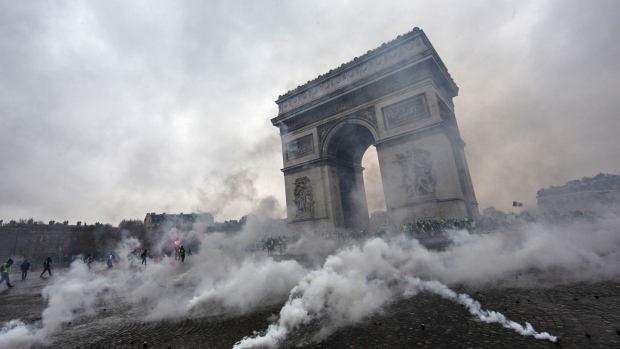 PARIS, FRANCE - DECEMBER 01: A paving stone hurtles toward riot police as they clash with protesters during a 'Yellow Vest' demonstration near the Arc de Triomphe on December 1, 2018 in Paris, France. The third 'Yellow Vest' (gilets jaunes) rally in Paris over increased fuel taxes and leadership in the government today caused over 150 arrests in the city with reports of injuries to protesters and security forces from violence that irrupted from the clashes. (Photo by Veronique de Viguerie/Getty Images)