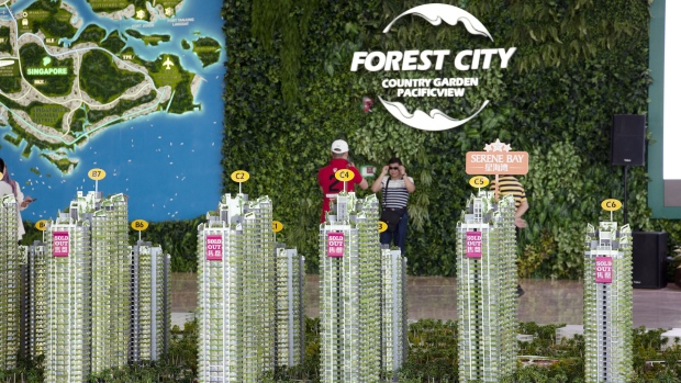 "Signs reading ""Sold Out"" are displayed on model towers of the Forest City development at the Country Garden Holdings Co. property showroom in Iskandar Malaysia zone of Johor Bahru, Johor, Malaysia, on Tuesday, Nov. 02, 2016. While Chinese home buyers have sent prices soaring from Vancouver to Sydney, in this corner of Southeast Asia it's China's developers that are swamping the market, pushing prices lower with a glut of hundreds of thousands of new homes. They're betting that the city of Johor Bahru, bordering Singapore, will eventually become the next Shenzhen."