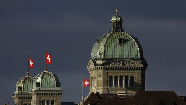 Swiss national flags fly above the Federal Palace, Switzerland's parliament building, in Bern, Switzerland, on Monday, Jan. 1, 2018. The supply of uninhabited apartments for rent has increased faster than the Swiss population has grown.