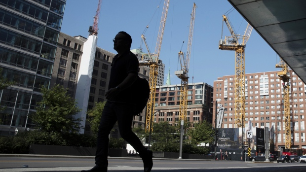 A pedestrian walks past cranes at a construction site in Montreal, Quebec, Canada, on Monday, Aug. 20, 2018. Median single-family home prices in Montreal rose 5.7% to C$336,250 in July from a year ago, according to the Greater Montreal Real Estate Board (GMREB).