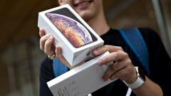 A customer displays an Apple Inc. iPhone XS Max box during a sales launch at a store in Chicago, Illinois, U.S., on Friday, Sept. 21, 2018.