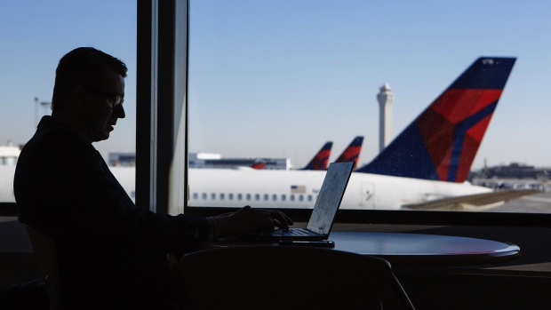 A traveler works on a laptop computer as Delta Air Lines Inc. planes are seen outside a window at Salt Lake City International airport (SLC) in Salt Lake City, Utah, U.S., on Friday, July 6, 2018. Delta Air Lines Inc. is scheduled to release earnings figures on July 12.